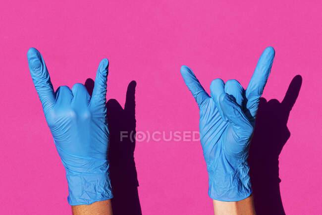 Руки жінки в латексних рукавичках, що роблять знак рогів. — стокове фото