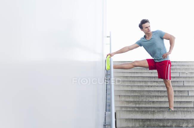 Красивый взрослый мужчина, растягивающий ногу на стене, стоя над ступеньками — стоковое фото