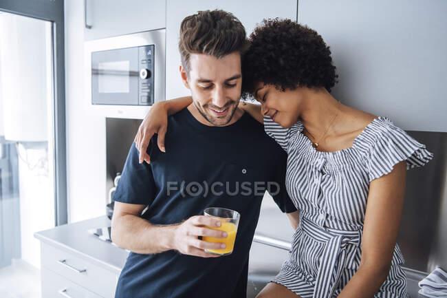 Romántica pareja multiétnica en cocina de ático - foto de stock