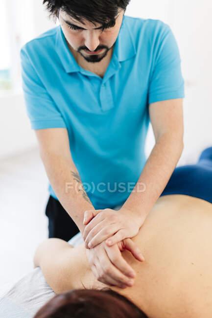 Fisioterapeuta con discapacidad visual masajeando la espalda de la mujer en la clínica - foto de stock