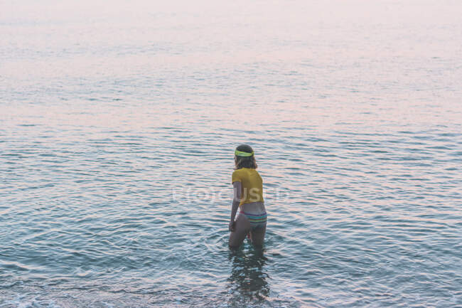 Vista posteriore di adolescente godendo in mare durante l'alba — Foto stock