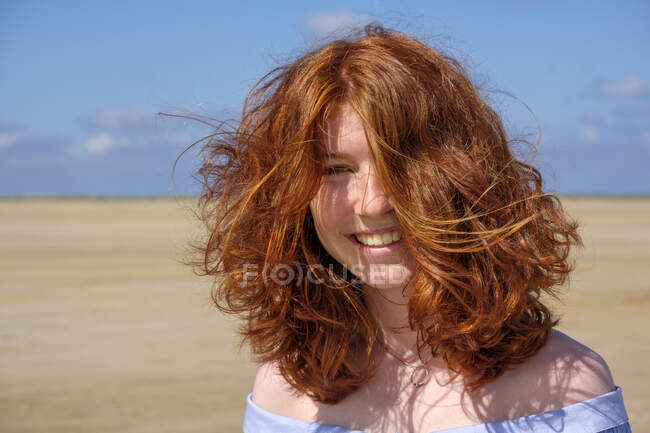 Close-up portrait of carefree redhead teenage girl standing at beach against sky on sunny day — Stock Photo