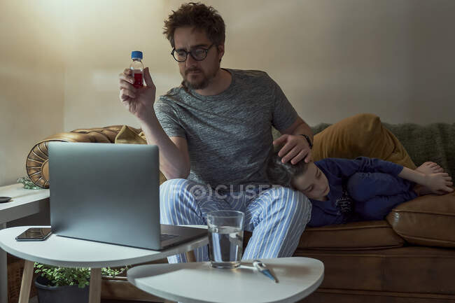 Uomo discutendo telemedicina con il medico tramite videochiamata attraverso il computer portatile mentre seduto da figlia malata in soggiorno a casa — Foto stock