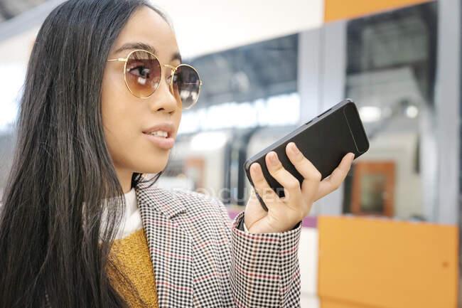 Primer plano de la mujer con gafas de sol hablando por teléfono inteligente en la estación de tren - foto de stock