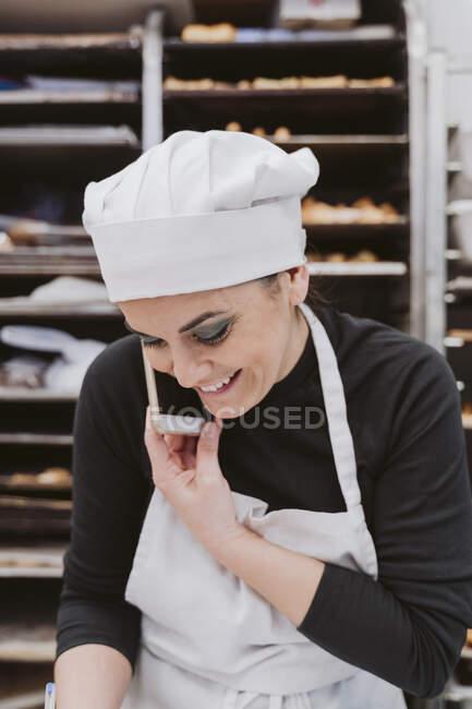 Padeiro fêmea feliz usando telefone inteligente na cozinha comercial — Fotografia de Stock