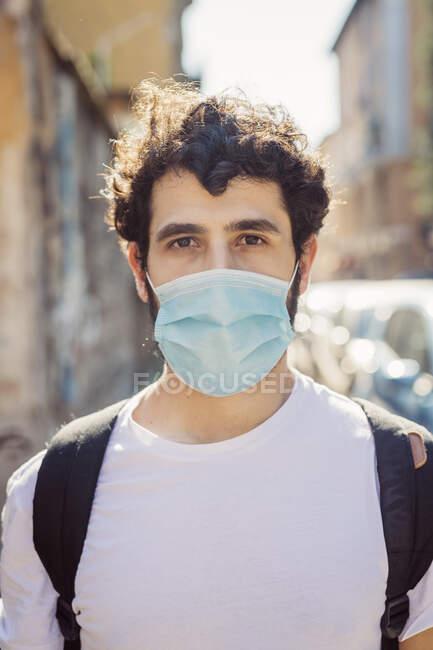 Портрет молодого чоловіка у масці, що стоїть надворі. — стокове фото