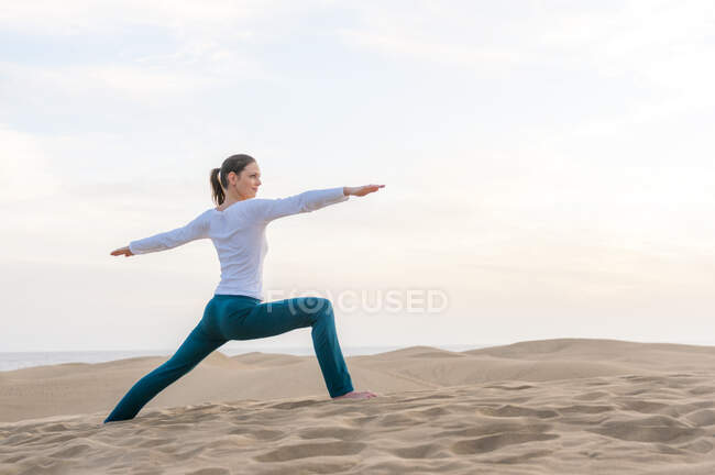 Женщина, практикующая йогу на закате в дюнах, Гран-Канария, Испания — стоковое фото