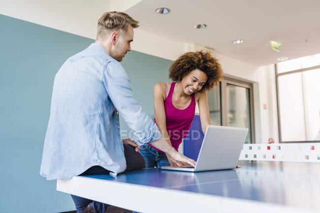 Молоді бізнесмени, які зустрічаються в сучасному офісі, користуються ноутбуком. — стокове фото