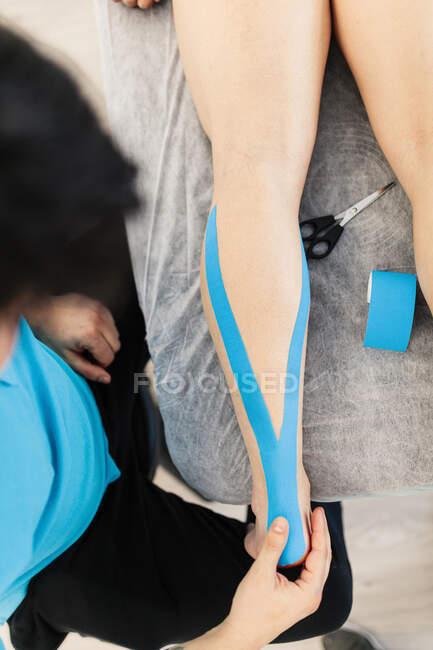 Fisioterapeuta con discapacidad visual que aplica cinta Kinesio en la pierna del niño en la clínica - foto de stock