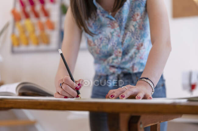 Young female trainee drawing design at workbench in atelier — Stock Photo
