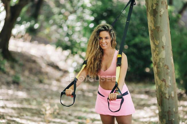 Sorrindo jovem mulher puxando tiras enquanto estava em pé no parque — Fotografia de Stock