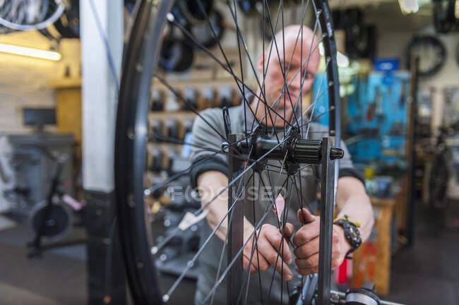 Велосипедна механіка працює в велосипедній майстерні. — стокове фото