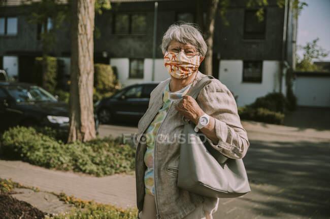 Mujer mayor que usa mascarilla mientras está de pie al aire libre en un día soleado durante un brote pandémico - foto de stock