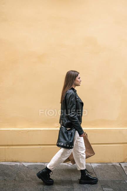 Jovem com sacos de compras andando na cidade — Fotografia de Stock