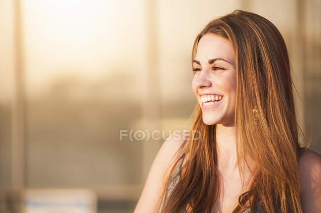 Bella giovane donna con lunghi capelli castani sorridenti durante la giornata di sole — Foto stock