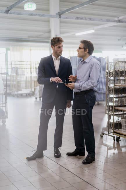 Два бізнесмени з планшетом на зібранні в пральні. — стокове фото