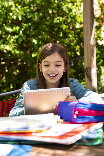 Girl sitting at garden table doing homework and using tablet — Stock Photo