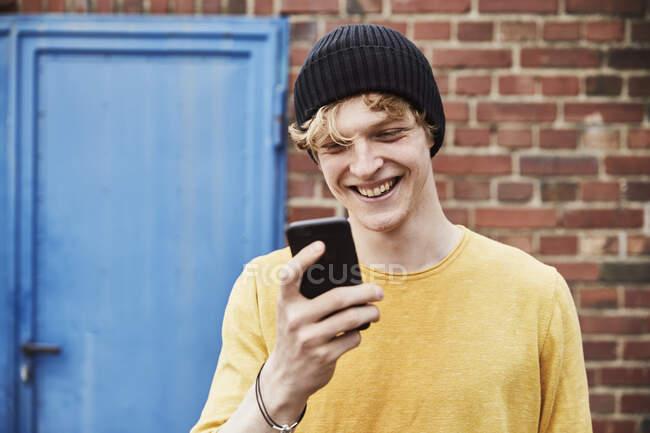 Ritratto di giovane felice che indossa un cappello guardando lo smartphone davanti al muro di mattoni — Foto stock