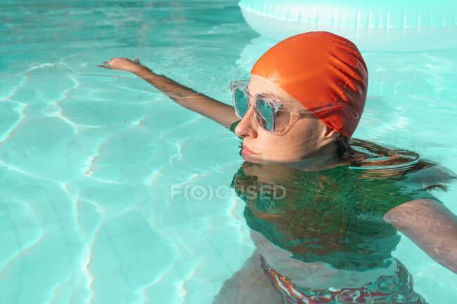 Retrato de mujer en piscina con gorra roja, jersey de punto verde y gafas de sol espejadas - foto de stock