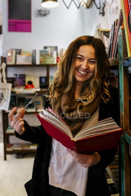 Femme souriante lisant un livre dans un café — Photo de stock