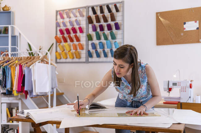 Beautiful young female designing trainee drawing on paper at workbench in studio — Stock Photo