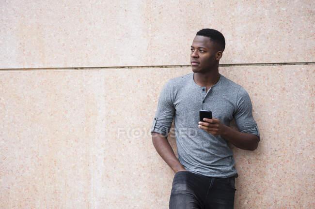 Joven usando el teléfono inteligente y de pie cerca del edificio - foto de stock
