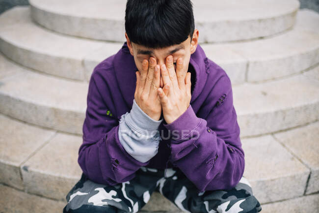 Tired young man rubbing eyes while sitting on steps — Stock Photo