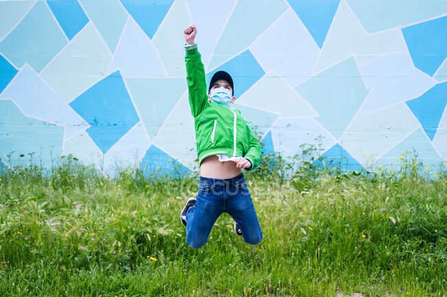 Niño usando máscara protectora y saltando en el prado - foto de stock