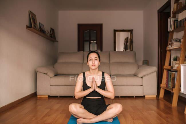 Уверенная женщина медитирует в молитвенной позе дома — стоковое фото