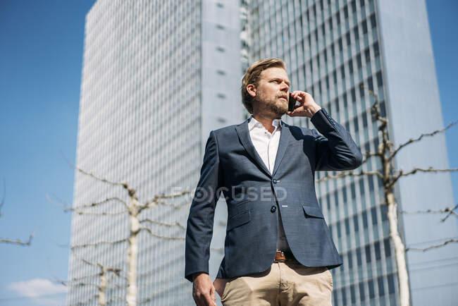 Retrato del hombre de negocios al teléfono en la ciudad - foto de stock