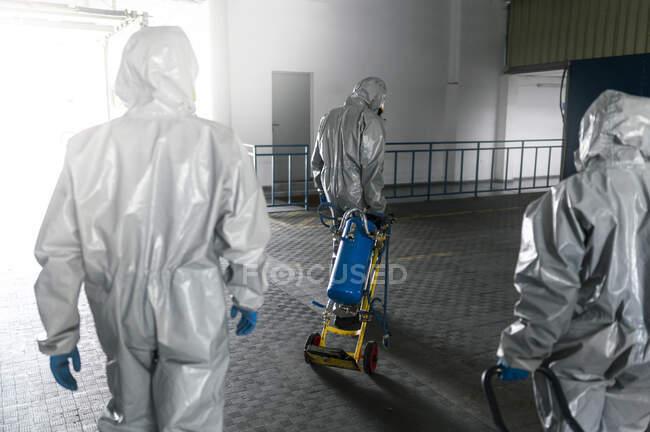 Vista trasera de los trabajadores de saneamiento caminando con químicos de descontaminación - foto de stock