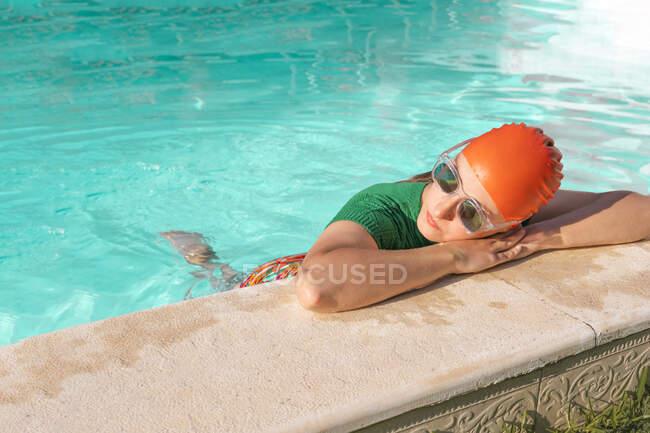 Mujer con gorra de natación roja y gafas de sol apoyadas en la piscina - foto de stock
