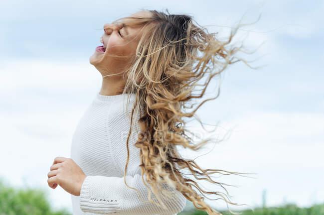Seitenansicht des fröhlichen blonden Mädchens, das gegen den Himmel spielt — Stockfoto