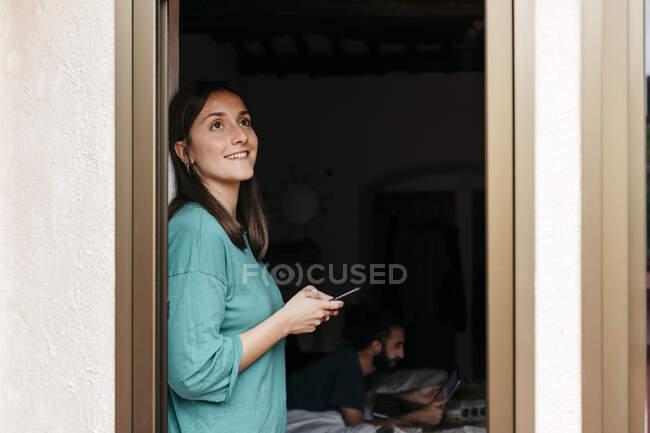 Женщина, использующая смартфон у открытого окна, мужчина, лежащий на кровати дома — стоковое фото