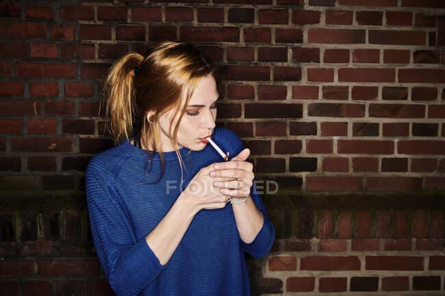 Mujer joven encendiendo cigarrillo contra la pared de ladrillo en la noche - foto de stock