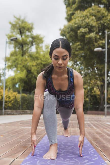 Молодая гибкая женщина практикующая йогу на коврике в парке — стоковое фото