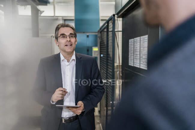 Deux hommes d'affaires en réunion dans une usine — Photo de stock