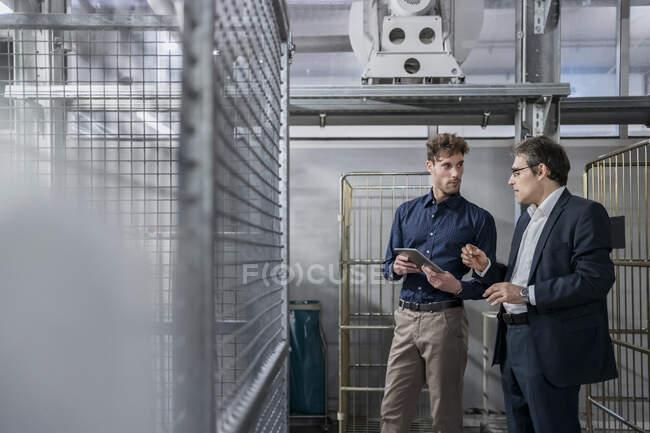 Due uomini d'affari con tablet che hanno una riunione in una fabbrica — Foto stock