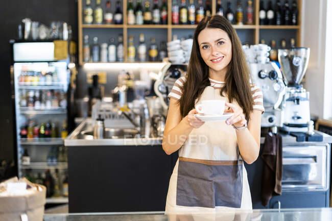 Чудовий молодий власник тримає кавову чашку і тарілку, стоячи у кафе. — стокове фото