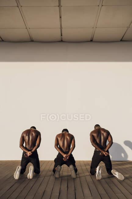 Tres hombres cruzando las manos a sus espaldas, arrodillados sobre tablones - foto de stock