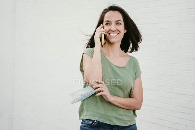 Retrato de mulher feliz ao telefone com máscara protetora — Fotografia de Stock