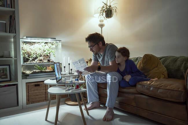 Хвороба, яка сидить за рецептом батька, обговорюючи це з лікарем через відео вдома. — стокове фото