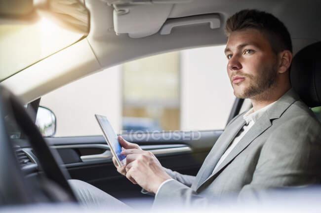 Junger Geschäftsmann nutzt Tablet im Auto — Stockfoto