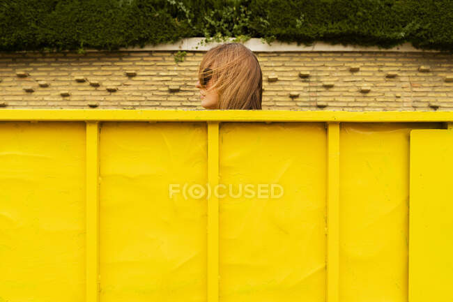 Head of woman sticking out of yellow container — Stock Photo