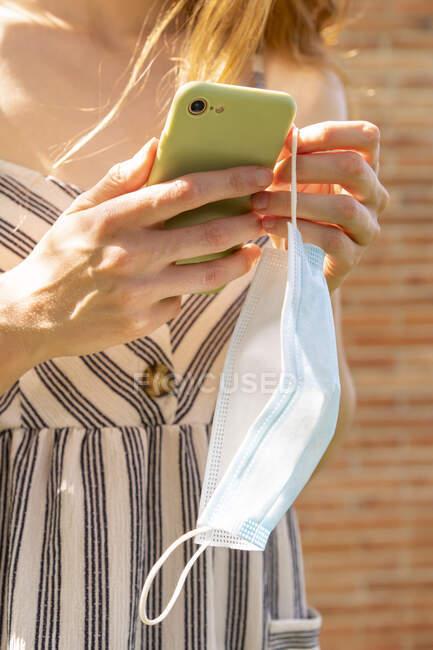 Close-up de jovem segurando máscara usando telefone inteligente enquanto está ao ar livre — Fotografia de Stock