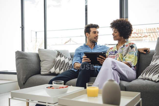 Багатоетнічна пара використовує цифрову табличку, сидячи на дивані в сучасному пентхаусі. — стокове фото