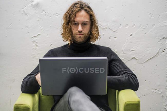 Jeune homme barbu utilisant un ordinateur portable assis sur un fauteuil contre un mur à la maison — Photo de stock