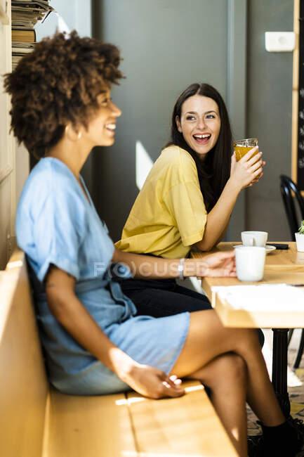 Mujer alegre sosteniendo bebida mientras busca amigo en la cafetería - foto de stock