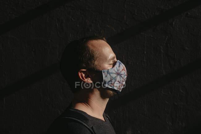 Gros plan de l'homme mi-adulte avec les yeux fermés portant un masque contre le mur — Photo de stock