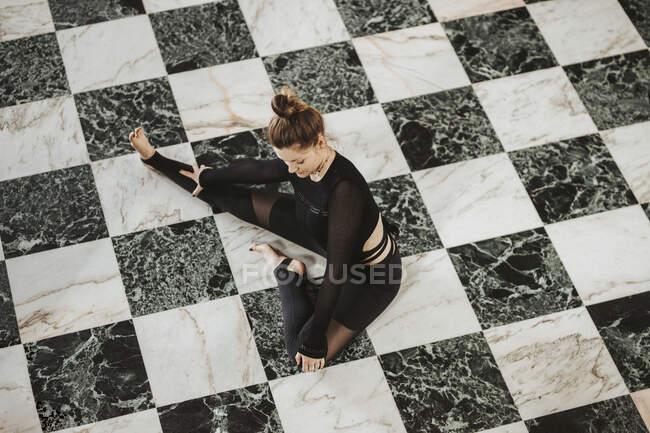 Mujer practicando yoga en suelo blanco y negro en casa - foto de stock